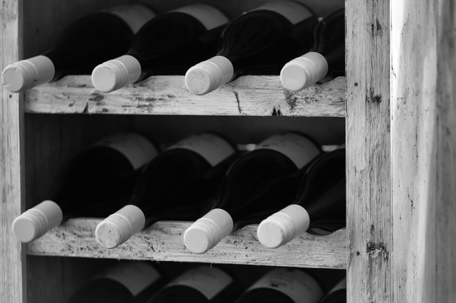 Wine bottles with white cork lying in row in wooden shelf