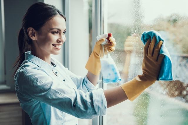 Young Smiling Woman Washing Window With Sponge. Happy Beautiful